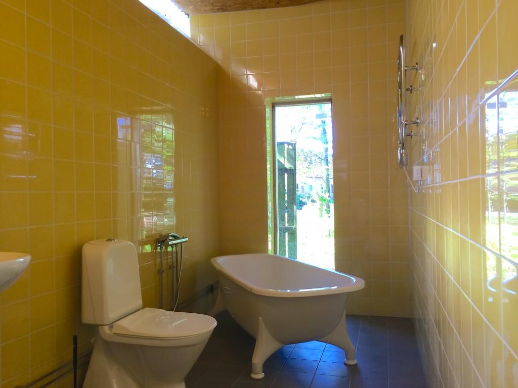 Helkaklat badrum med fönster och badkar